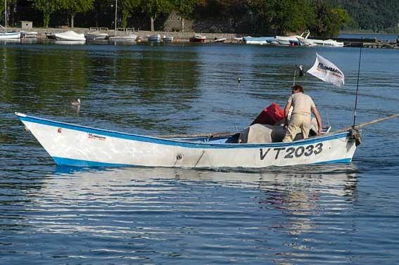Un pescatore con la sua barca a Marta sul lago di Bolsena